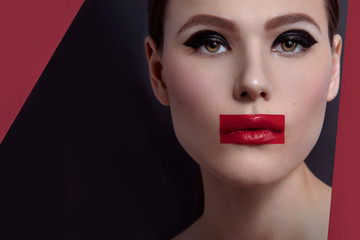 High fashion, beauty portrait of young woman model with avant garde fashion art makeup. Red lips