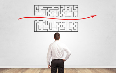 Wall Mural - Businessman in doubt looking to a maze and searching the way out