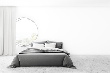 Minimalistic white bedroom with round window