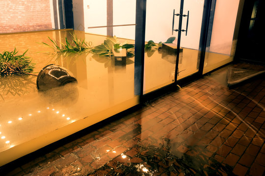 Water flowing through doors from a flooded office. Effects Tropical depression Imelda. Houston, Texas, US