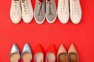 Flat lay composition with different bright shoes on red background. Space for text