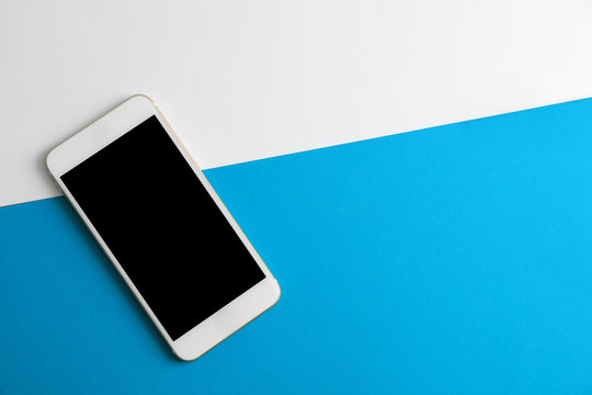 Modern phone on color background, top view. Space for text