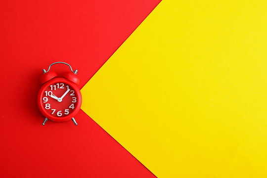 Modern alarm clock on color background, top view. Space for text