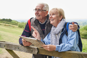 Retired Senior Couple On Walking Holiday Resting On Gate Looking At Map