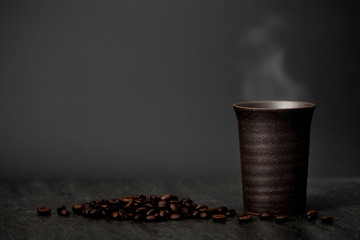 Classic still life - a cup of coffee with smoke and roasted coff