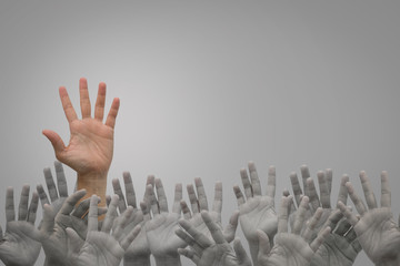 Group of human hands raised high up on grey