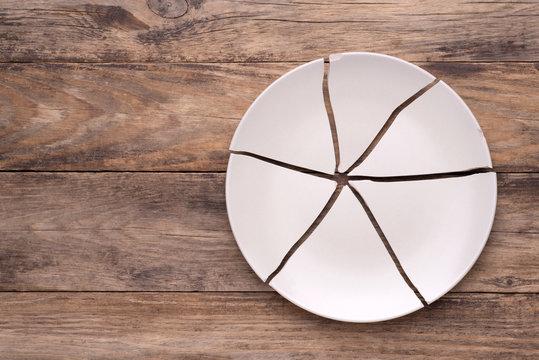 Broken plate on wooden background, top view