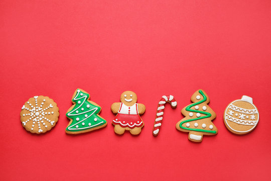 Flat lay composition with tasty homemade Christmas cookies on red background, space for text