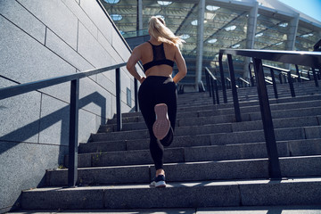 Bottom of running sneaker shoe, woman running on a stairs