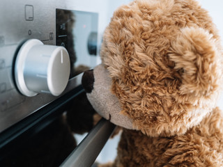 Brown teddy bear, is watching how the oven goes in the kitchen