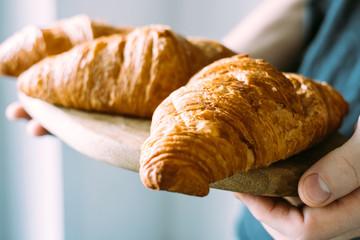 Fototapeten Brot Fresh croissants on a wooden tray