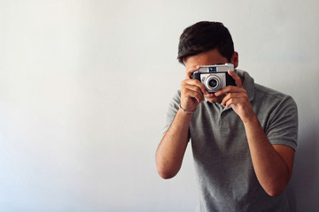 Man dressed in gray and in a hat taking some pictures with his camera.