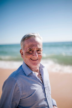 Portrait of 70 year old man with spots on the skin that is on the beach