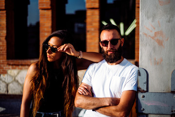 Couple of man and woman posing at sunset with sunglasses.