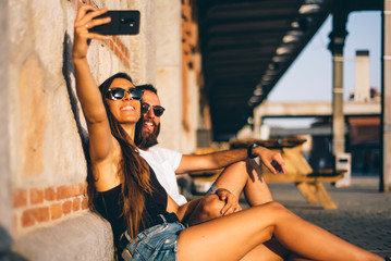 Couple of man and woman sunset by city make selfie with mobile phone.