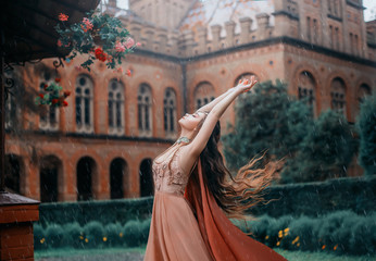 Lady with a pretty face, stands under the rainy sky and reaches out to meet the drops. Young magician in a orange dress with a cape near the castle. Dance with the wind, long hair flying, fluttering.