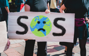 """The word """" SOS """" and sad earth picture drawn on a carton banner in woman's hand. Protest for climate change. Human holds a cardboard with an inscription: SOS. Save the Earth"""