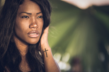 A beautiful, thoughtful African-American woman with a tattoo in her hand with an unfocused natural background