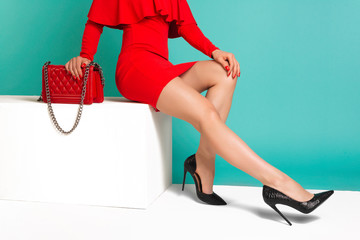 Sexy woman in high heels with red handbag on a blue background.