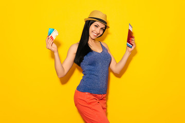 Young smiling student holding passport pass ticket and credit card isolated on yellow background.