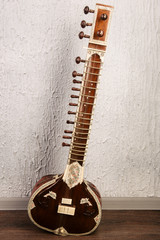Indian musical instrument sitar standing next to the grey wall