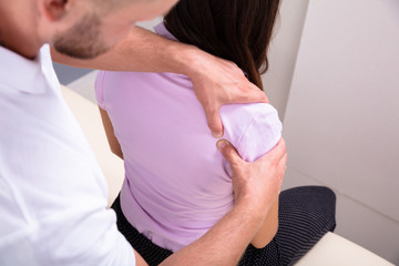 Male Physiotherapist Giving Shoulder Massage To Woman