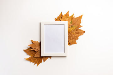 Autumn composition. Photo frame, maple leaves, on white background. Flat lay, top view, copy space.