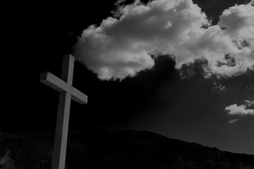 Close up cement cross(Jesus Christ crucifix) with mountain ranges background, thick white clouds on the top of the rood crucifix. Black and white image.