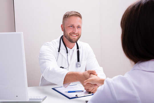 Female And Male Doctor Sitting At Desk Shaking Hands
