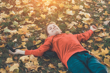Happy boy resting in a park lying on his back. Lawn with autumn foliage. Sunny day
