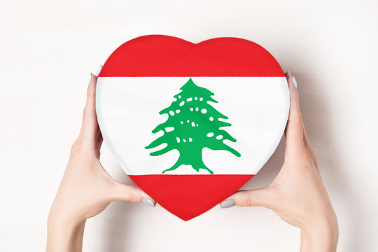 Flag of Lebanon on a heart shaped box in a female hands. White background