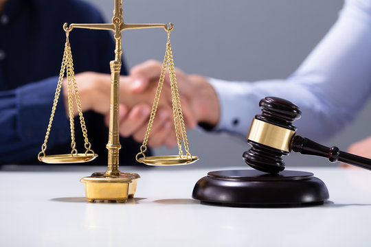 Gavel And Golden Justice Scale In Front Of Shaking Hands