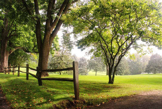 Early autumn foggy morning landscape. Scenic view with deep fog over a golf course with wooden fence in a foreground. Midwest USA, Wisconsin.