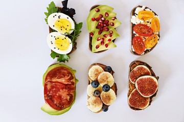 Six different toasts on the white background. Assorted toasts with eggs, fruits and berries,...