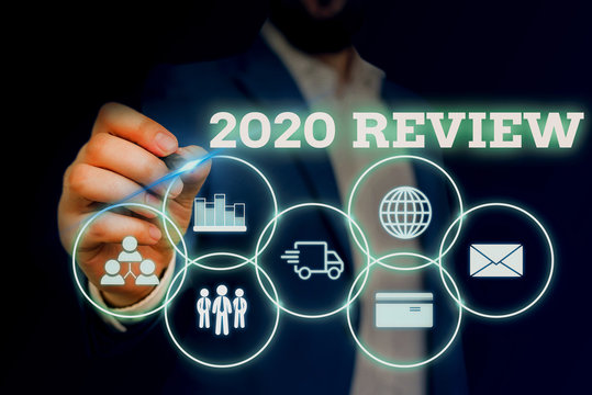 Handwriting text writing 2020 Review. Conceptual photo seeing important events or actions that made previous year Male human wear formal work suit presenting presentation using smart device