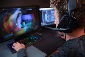 Teenage gamer using a computer to play video games online