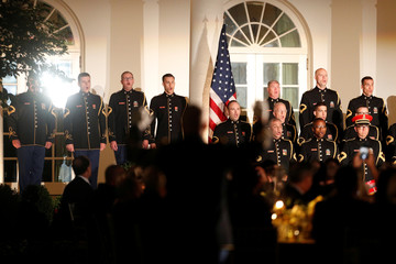 "Government officials and guests participate in viewing a performance by ""The President's Own"" United States Marine Corps band, inside the Rose Garden of the White House in Washington, D.C."