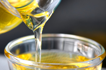 Pouring olive oil in the a glass bowl at stone kitchen. Prepare for cooking concept. Healthcare and Beauty Concept.
