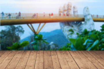 Empty wood plank perspective with abstact blur golden hand bridge on bana hill resort in background for product advertise.