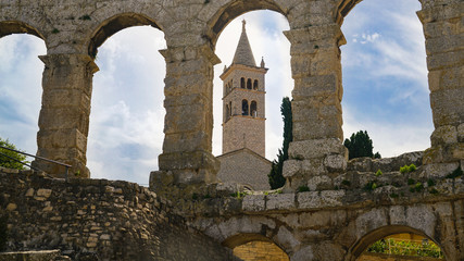 The bell tower of the monastery of St. Antoine in the opening of the wall of the amphitheater in the city of Pula