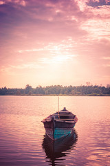Canoe in lake at sunset