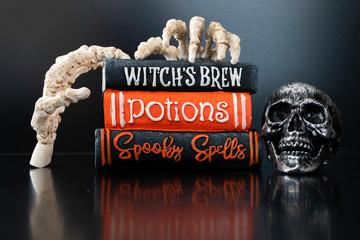Halloween Skeleton hands holding magic books for Halloween