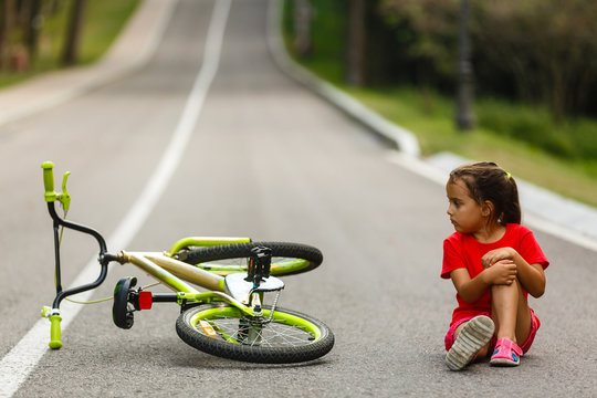 The little girl fell off the bike on the road