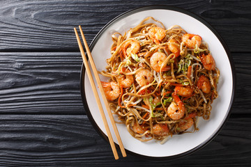 Authentic chow mein noodle fried with shrimp, vegetables and sesame seeds close-up on a plate. Horizontal top view