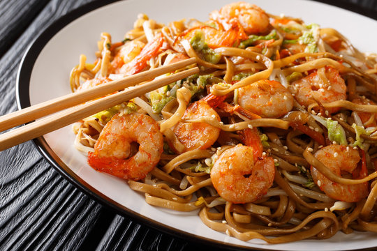 Chinese food chow mein noodles with shrimp, vegetables and sesame seeds close-up on a plate. horizontal