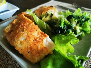 Fried fish. Breaded walleye fillet. Garnish with broccoli and green vegetables. Home dinner.