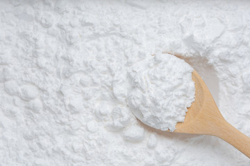 Close-up of tapioca starch or flour powder in wooden spoon with starch background