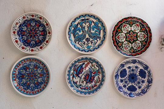 Traditional greek ceramic plate on white wall in a street . Kos island, Greece