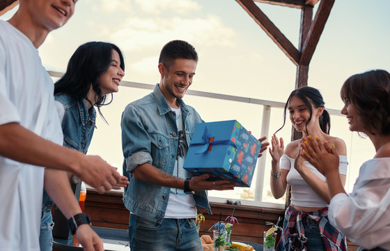 Celebrating birthday. Young happy man is receiving a gift from his friends while standing on the roof