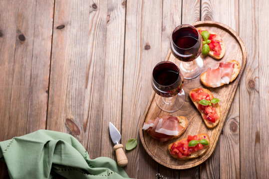 Two glasses of red wine and bruschetta, appetizer set on wooden tray, wooden rusitc background